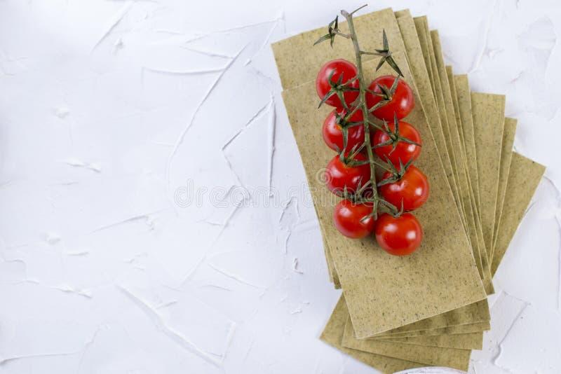 Hojas de los tomates de las lasañas y de cereza, en un fondo concreto blanco imagen de archivo