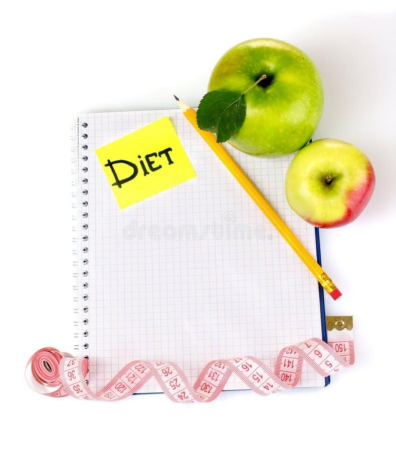 Hojas de operación (planning) de una dieta. Cuaderno, lápiz y manzanas fotografía de archivo libre de regalías