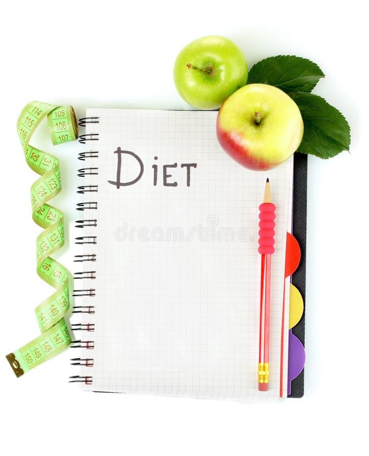 Hojas de operación (planning) de una dieta. Cuaderno, lápiz y manzanas fotos de archivo