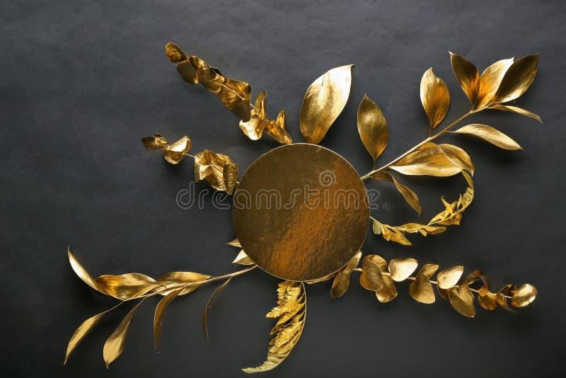 Hojas de oro con la tarjeta de felicitación en fondo negro imagen de archivo libre de regalías