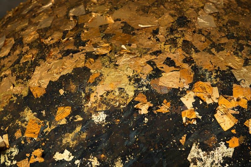 Hojas de oro pegadas en la superficie de las piedras redondas de Luuk Nimit para foto de archivo