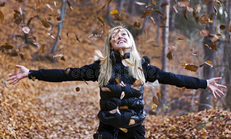 Hojas de otoño de la chica joven que lanzan foto de archivo libre de regalías