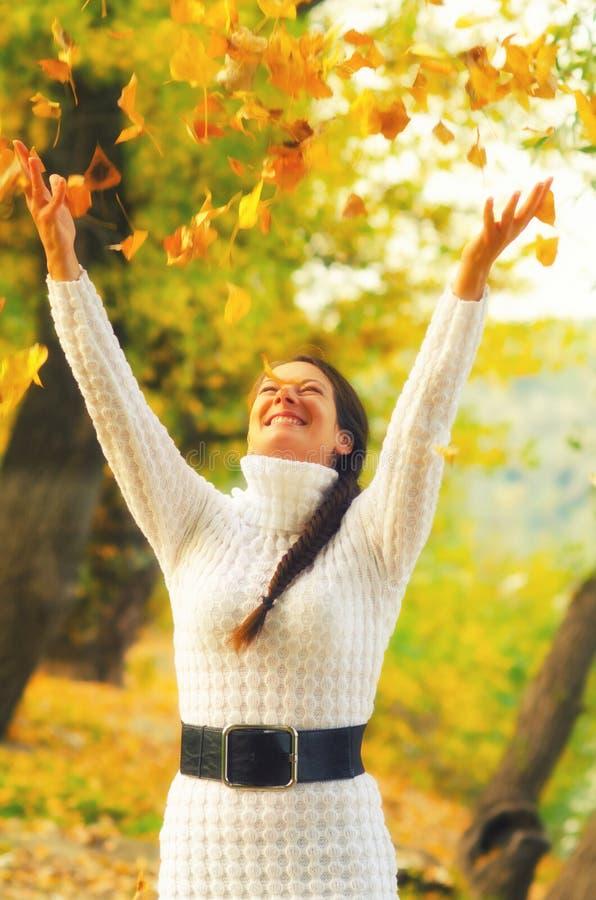 Hojas de otoño de la muchacha que lanzan en el aire fotos de archivo libres de regalías