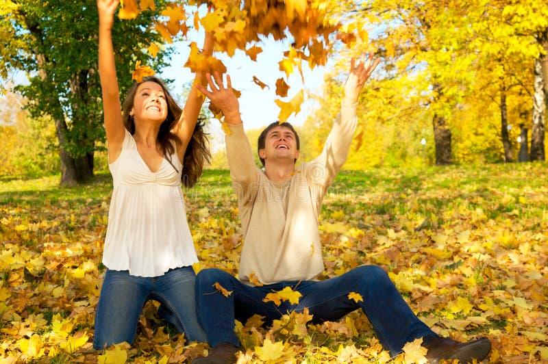 Hojas de otoño de los pares que lanzan jovenes fotos de archivo