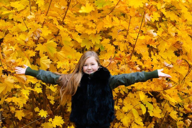 Hojas de otoño felices de la muchacha joven del adolescente imagenes de archivo