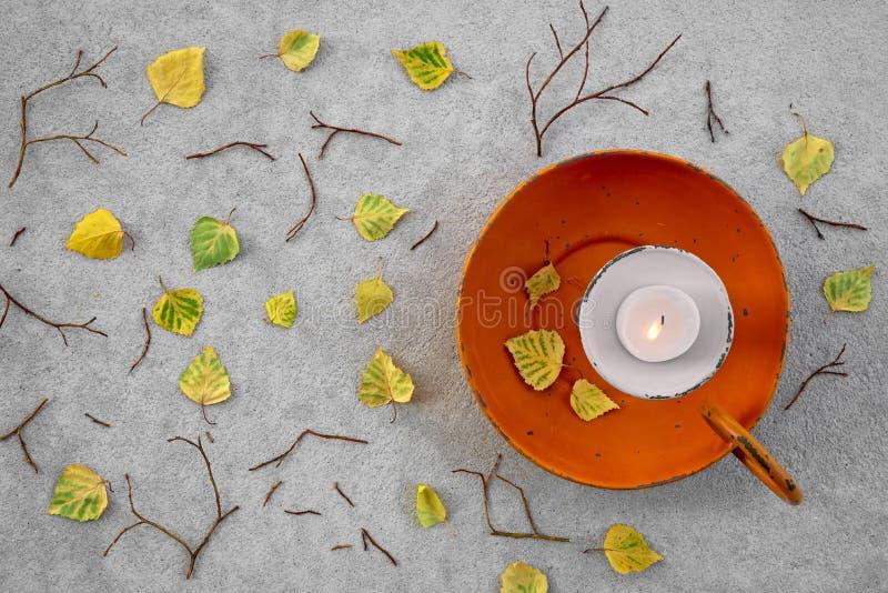 Hojas de otoño y luz de una vela acogedora fotografía de archivo libre de regalías