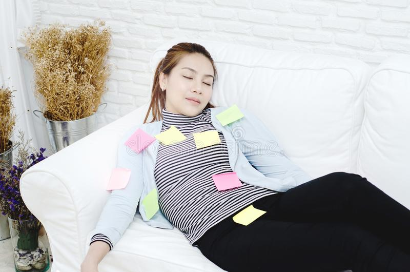 Hojas de papel amarillas, verdes y rosadas en la mujer que está durmiendo y agotado de trabajo foto de archivo libre de regalías