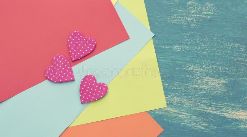 Hojas de papel coloreadas en un corazón decorativo pintado de madera Valentine' del fondo azul; día de s fotografía de archivo
