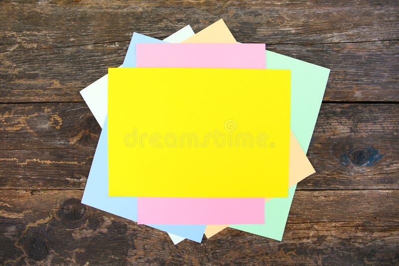 Hojas de papel coloreadas en viejo fondo de madera fotografía de archivo libre de regalías