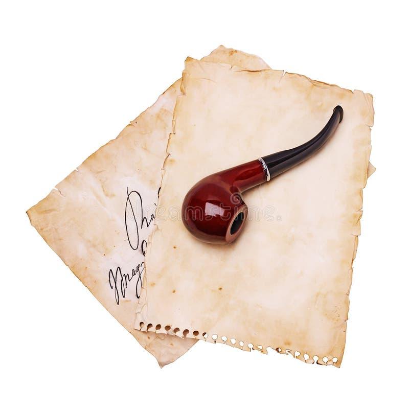 Hojas de papel viejas y tubo que fuma imagen de archivo