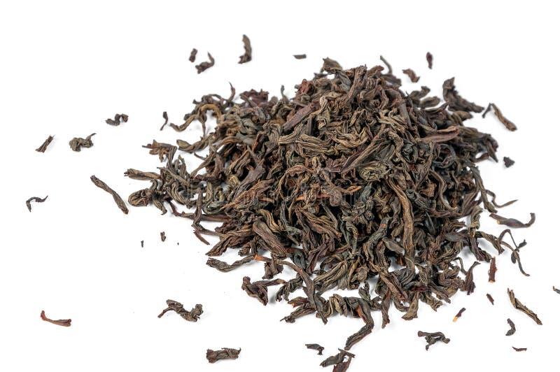 Hojas de té negras secas aisladas en el fondo blanco fotografía de archivo