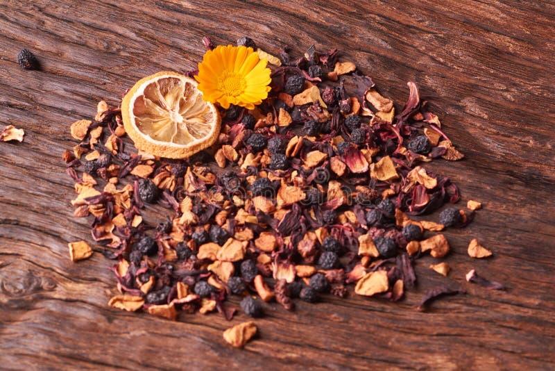 Hojas de té secas negras de la fruta en la tabla de madera Foco selectivo foto de archivo