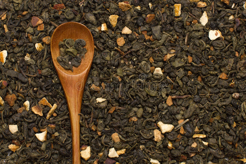 Hojas de té verdes con la fruta cítrica y las frutas con la cuchara de madera fotografía de archivo libre de regalías
