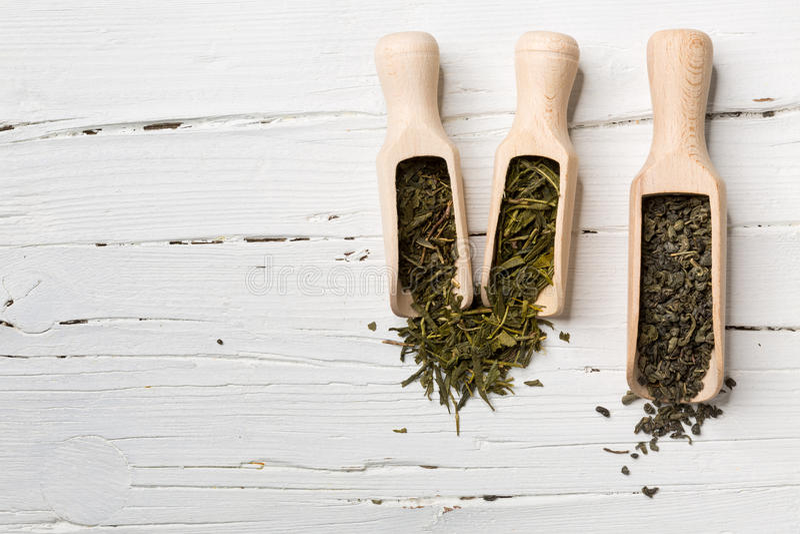 Hojas de té verdes en cucharada en el fondo de madera blanco foto de archivo