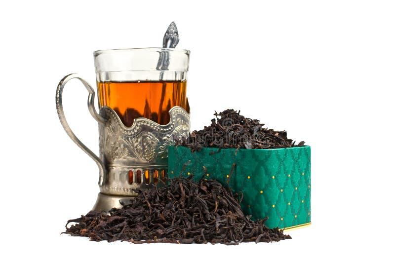 Hojas de té y vidrio secos imagen de archivo