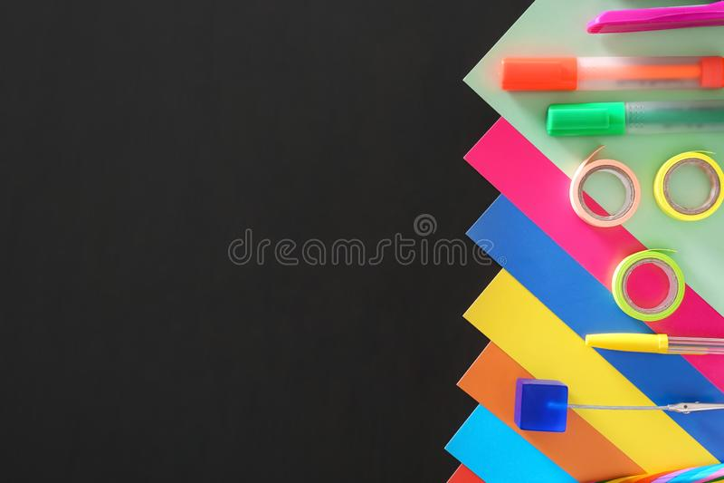 Hojas del cartón y efectos de escritorio coloridos de la escuela en fondo oscuro fotos de archivo libres de regalías