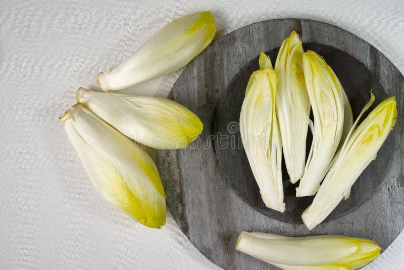 Hojas frescas de la ensalada de la achicoria colocadas en una piedra gris y una boa de madera foto de archivo libre de regalías