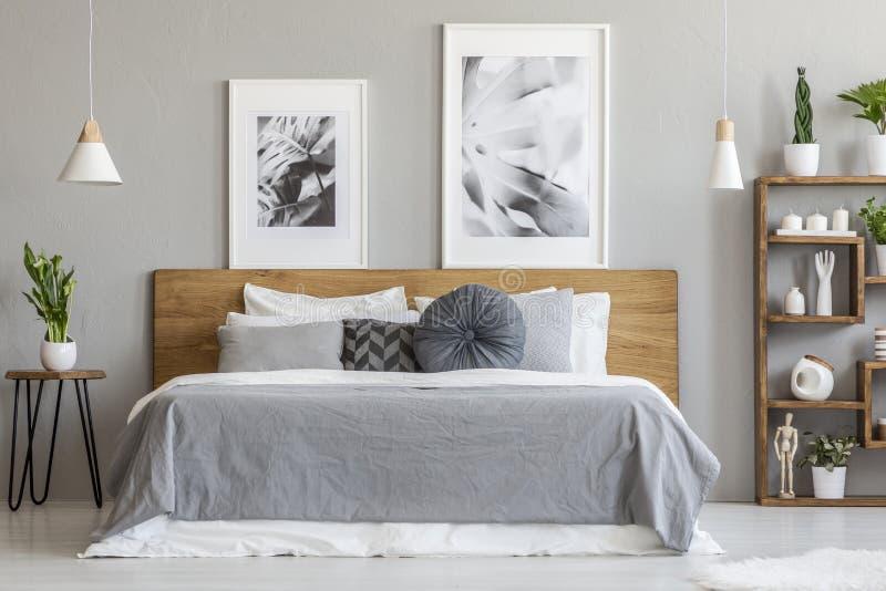 Hojas grises en cama de madera al lado de la tabla con la planta en interior del dormitorio con los carteles Foto verdadera fotos de archivo libres de regalías