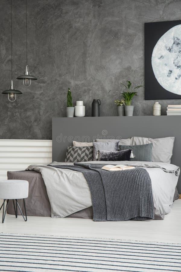 Hojas grises en cama en interior oscuro monocromático del dormitorio con p imagen de archivo