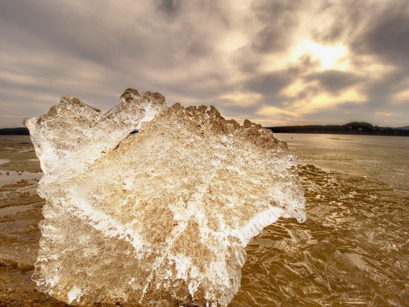 Hojas heladas que derriten en la playa arenosa Final de largo y el venir del invierno del crue Detalle de la masa de hielo flotan imágenes de archivo libres de regalías