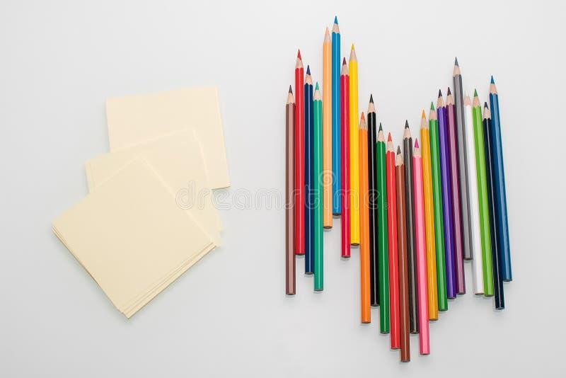 Hojas limpias para las notas y lápices del color en el espacio blanco de la copia de la opinión superior del fondo fotos de archivo