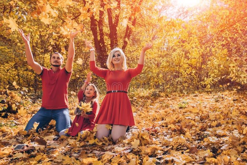 Hojas que lanzan de la familia feliz joven hermosa en día del otoño imagenes de archivo