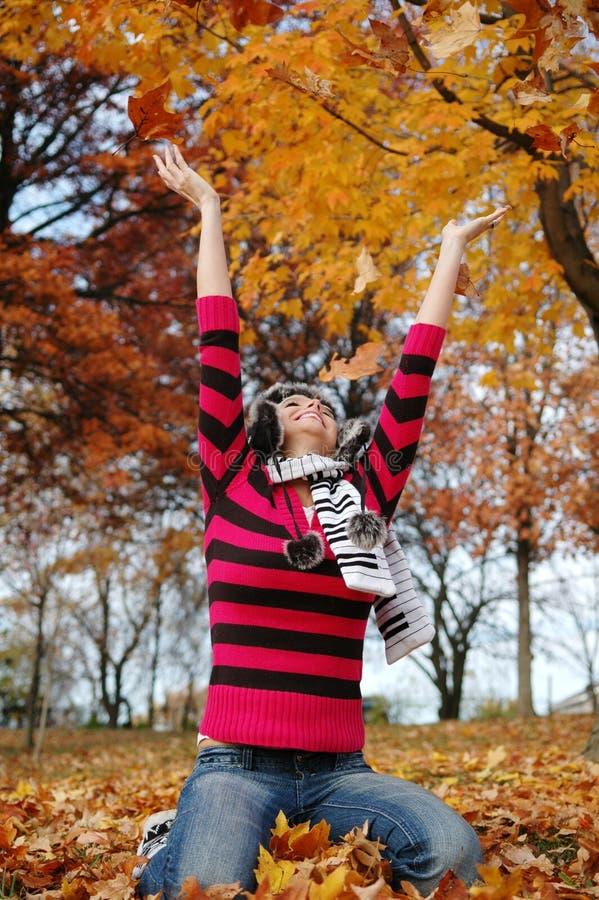 Hojas que lanzan de la muchacha del otoño imagen de archivo