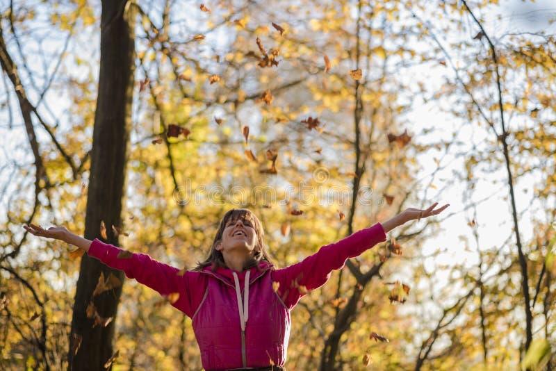 Hojas que lanzan felices de la mujer joven en el aire foto de archivo libre de regalías