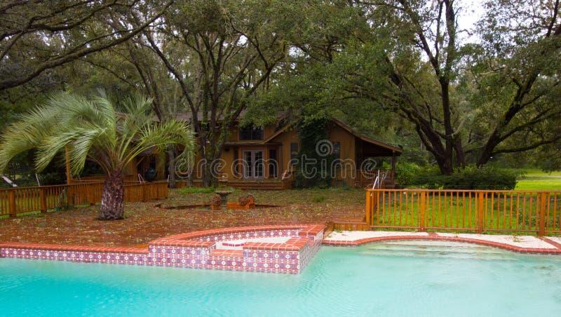 Hojas que soplan de una tormenta a través de la cubierta de la piscina de un hogar en ocala imagenes de archivo