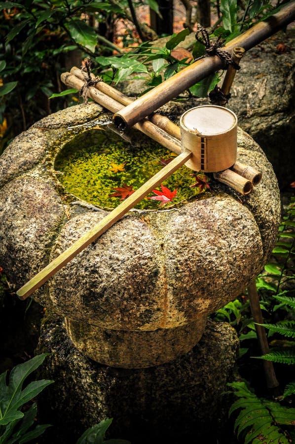 Hojas rojas en un lavabo de piedra lleno de agua equipado de un cazo de bambú imagenes de archivo