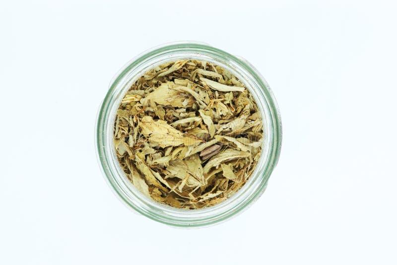 Hojas secadas del stevia en la botella aislada en el fondo blanco imagen de archivo libre de regalías