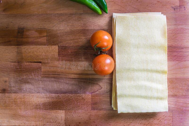Hojas, tomates y salchichones de las lasañas fotos de archivo