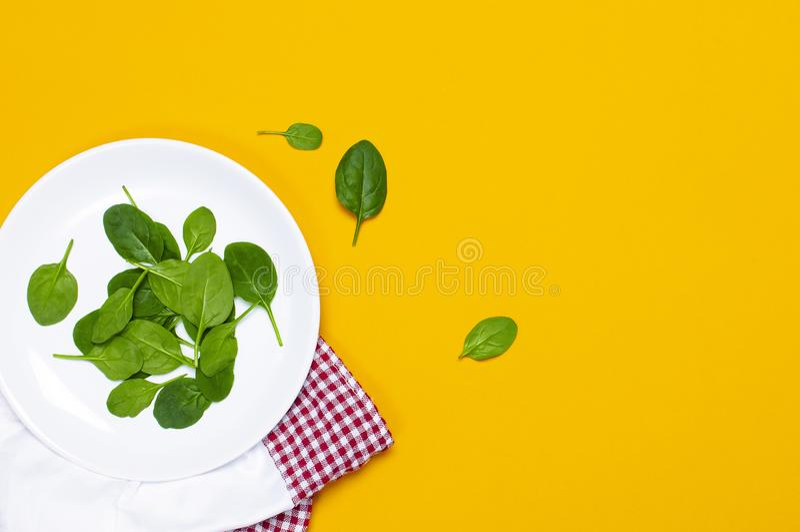 Hojas verdes frescas de la espinaca en la placa blanca en espacio puesto plano amarillo brillante de la copia de la opini?n super imagenes de archivo