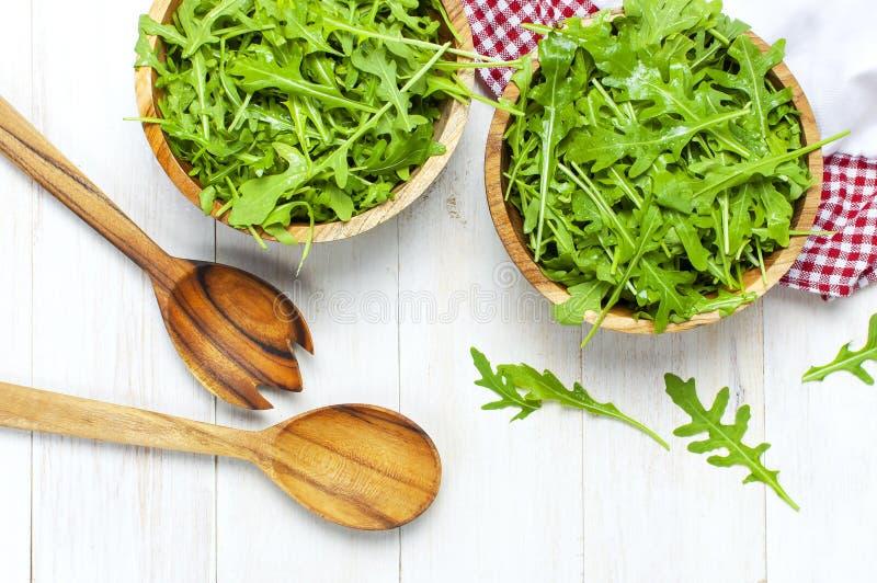 Hojas verdes frescas del arugula en el cuenco de madera, ensalada del rucola en la opini?n de top r?stica de madera blanca del fo imagenes de archivo