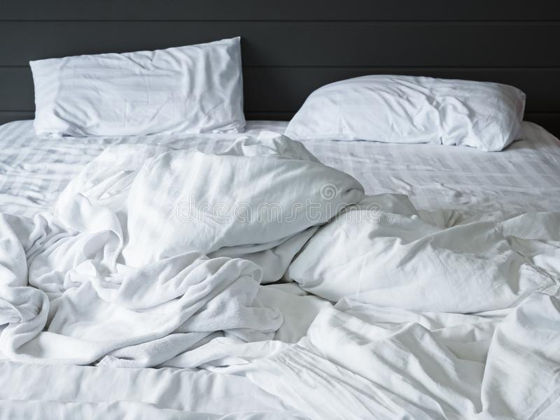 Hojas y almohada blancas sucias del lecho en el fondo del dormitorio, cama sucia sin hacer después del concepto del sueño de la c fotografía de archivo