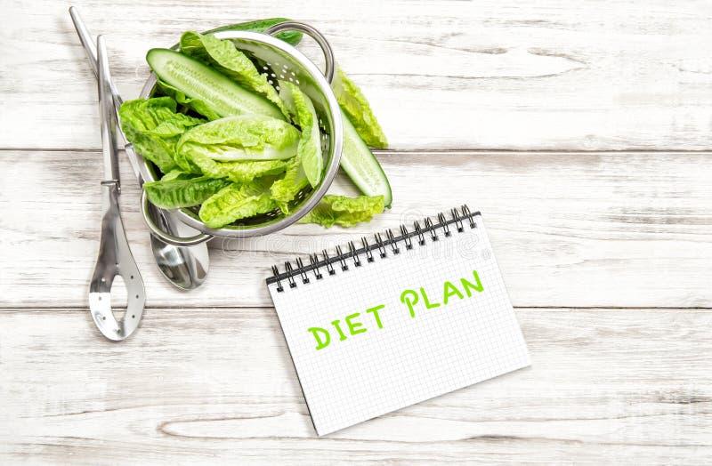 Hojas y verduras de la ensalada verde con el diario del plan de la dieta foto de archivo libre de regalías