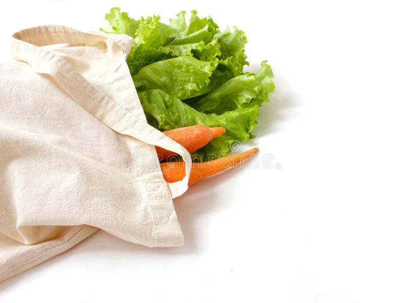 Hojas y zanahorias de la ensalada de la lechuga en un bolso de lino para hacer compras aislada imagenes de archivo