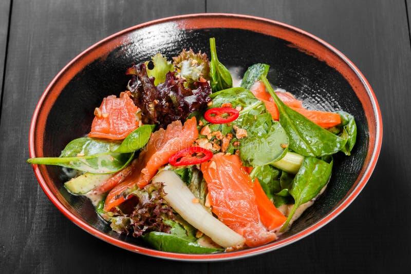 Hojea la ensalada vegetal con el salmón ahumado, la espinaca, pimientas, los pepinos y la salsa en la placa en fondo de madera os imagen de archivo