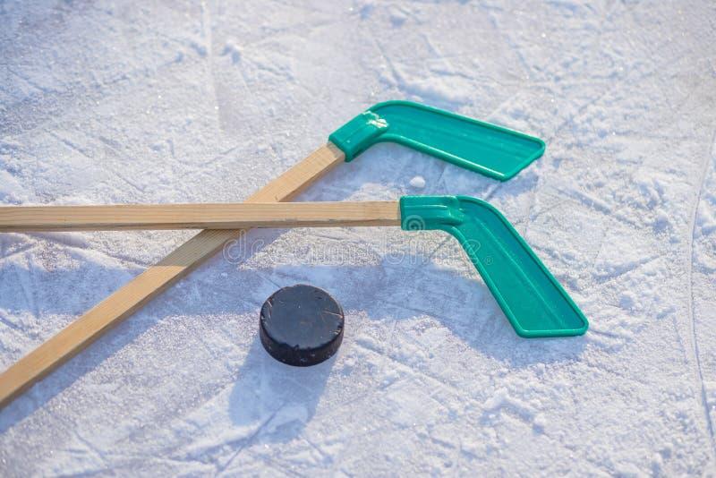 Hokejowy kij i krążek hokojowy na lodzie na pogodnym zima dniu zima sporty dla plenerowych aktywność hokejowego krążka hokojowego fotografia royalty free
