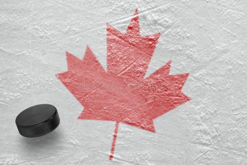 Hokejowy krążek hokojowy i liść klonowy zdjęcia royalty free