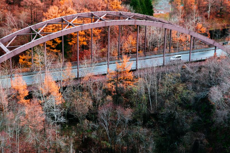 Hokkaido highway red truss bridge with autumn foliage yellow tree forest, aerial view stock image