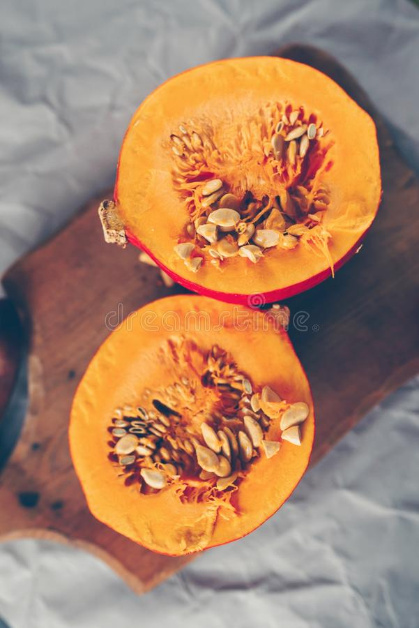 Hokkaido pumpkin cut in half. The halves are on a wooden background stock images