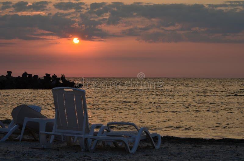 Holów krzesła na morze plaży przy wschodem słońca zdjęcia stock