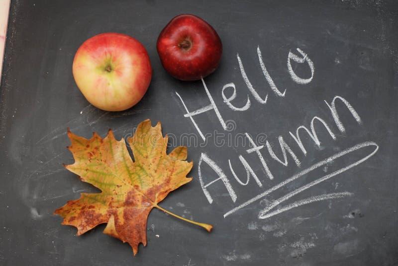 Hola otoño - la inscripción en la pizarra con la tiza y la manzana, hojas imagen de archivo