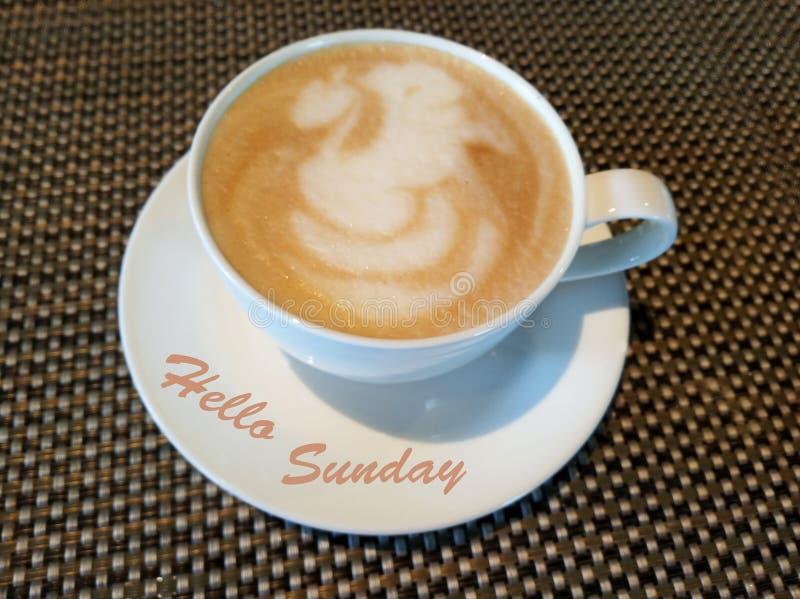 Hola saludos de domingo con una taza blanca de café y de fondo natural del modelo de la estera imagen de archivo libre de regalías