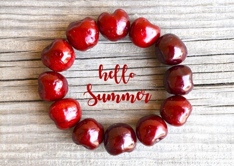 Hola tarjeta de felicitación del verano con las bayas rojas frescas de la cereza en viejo fondo de madera Concepto del verano imagen de archivo