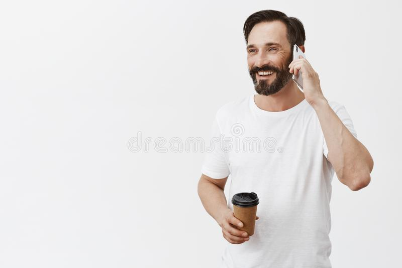 Hola vengo terminado he en café Hombre relajado alegre y contento que come la taza de café y que habla con el amigo vía smartphon imagenes de archivo