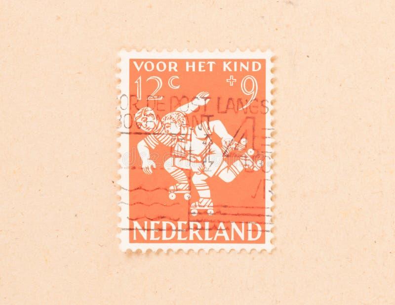 HOLANDIE 1960: Znaczek drukujący w holandiach pokazuje dzieci bawić się, około 1960 fotografia stock