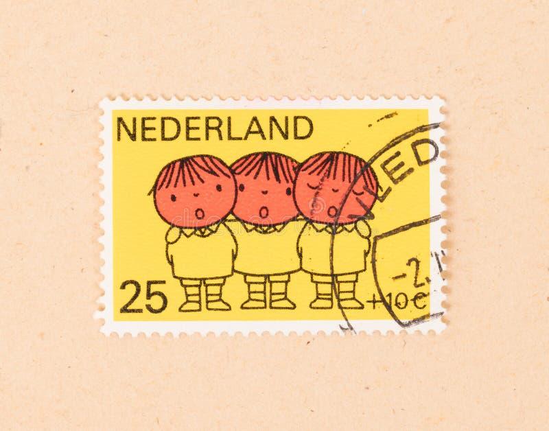 HOLANDIE 1960: Znaczek drukuj?cy w holandiach pokazuje trzy dziecka ?piewa, oko?o 1960 obraz stock