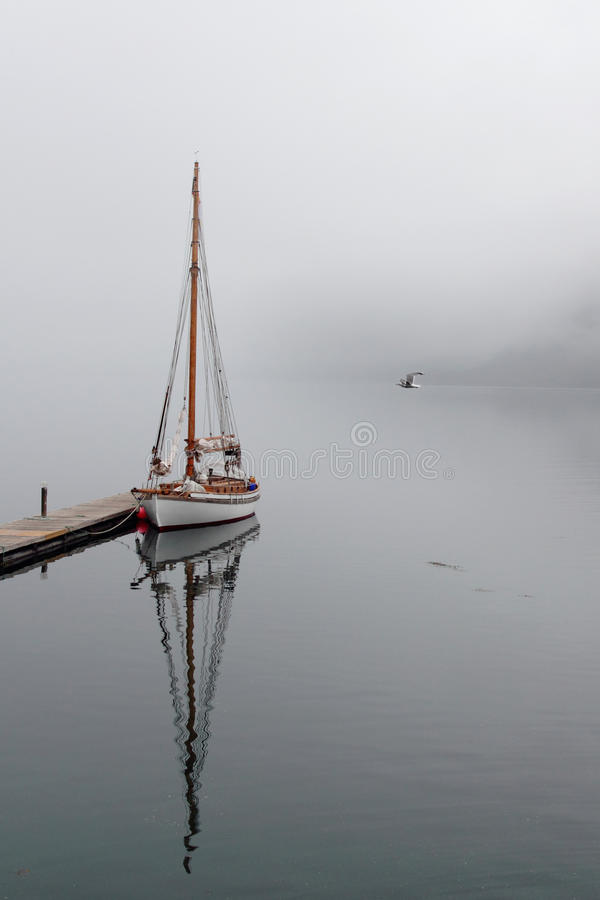 Holandsfjord mirrors. Sailboat mirroring in a foggy Holandsfjord, in front of Svartisen Glacier, the lowest glacier of europe stock photography